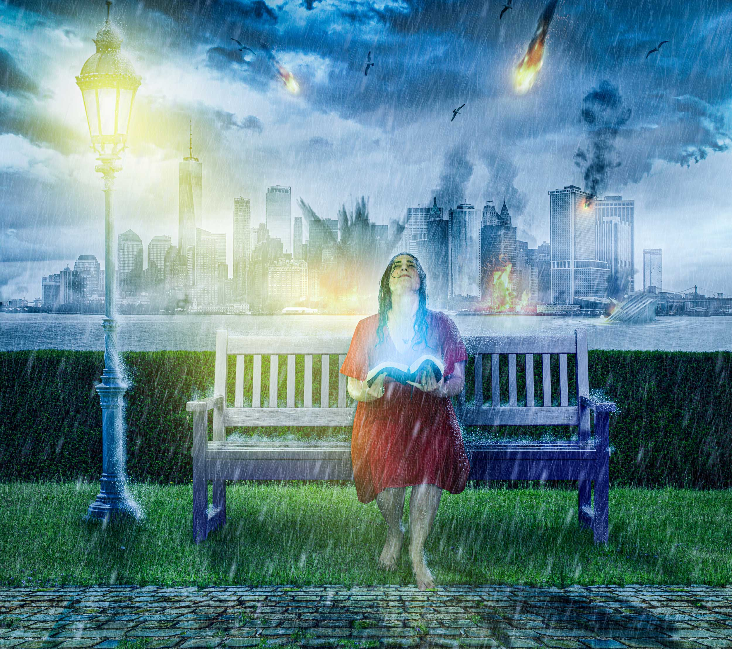A woman sits on a park bench in the rain, holding her Bible as a city is being destroyed behind her.
